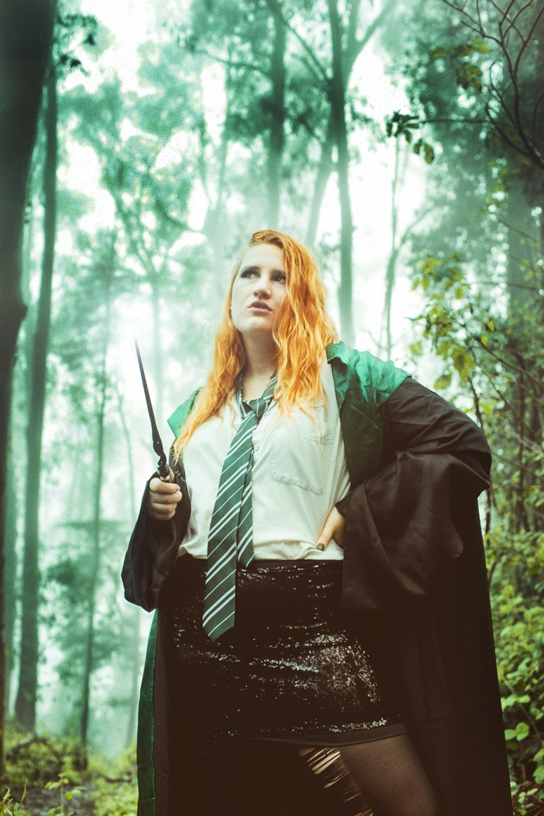 woman in Slytherin outfit and wand